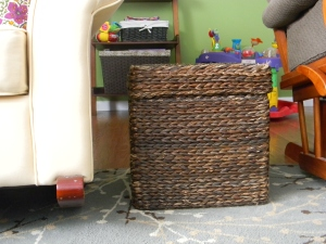 This shot is a good combination of our storage ideas. The wicker cube holds our dvds. The large basket on the shelf holds most of our board games. Then the other basket holds Emily's burp clothes.